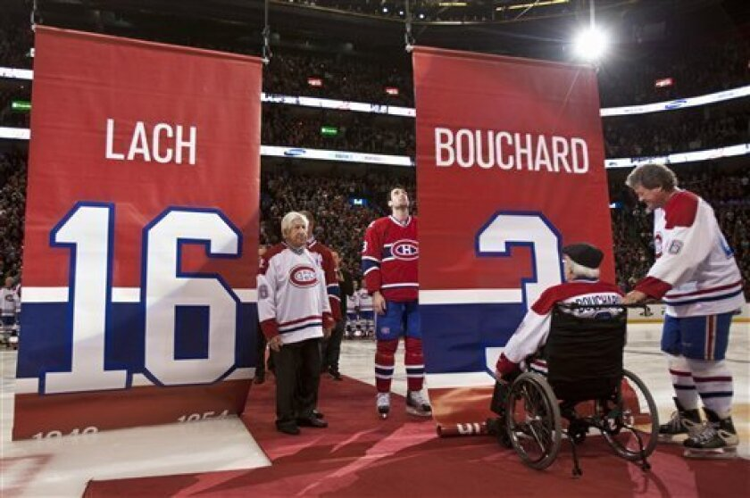 "Former Montreal Canadiens Elmer Lach, left, and Emile ""Butch"" Bouchard watch while their banners are raised as their numbers are retired during centennial celebrations Friday, Dec. 4, 2009 in Montreal. Helping Bouchard is his son Butch and Canadiens player Ryan O'Byrne looks on. (AP Photo/The Canadian Press, Paul Chiasson)"