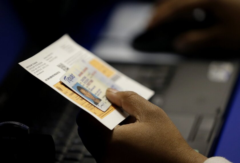 FILE - In this Feb. 26, 2014, file photo, an election official checks a voter's photo identification at an early voting polling site in Austin, Texas. A federal appeals court ruled Wednesday, July 20, 2016, that Texas' strict voter ID law discriminates against minorities and the poor and must quick