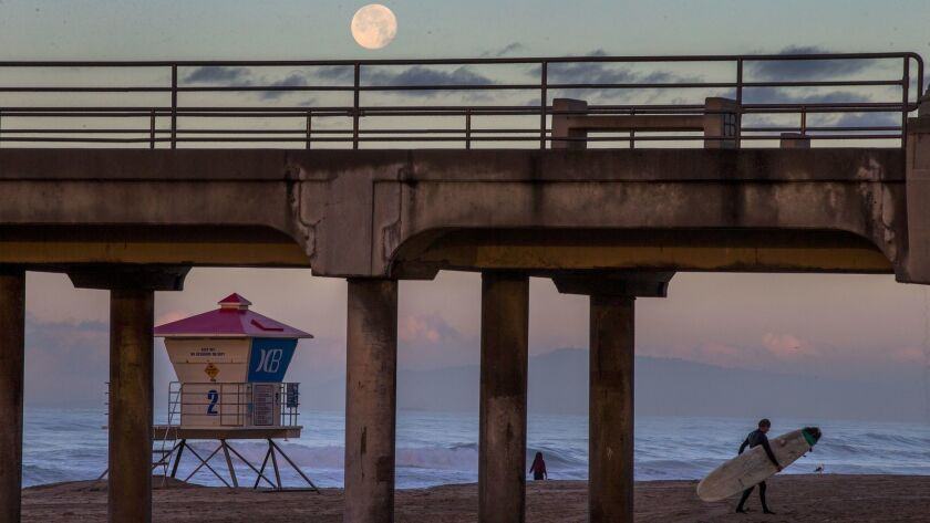A full moon sets over the Huntington Beach Pier at sunrise as a surfer exits the water. The City Council on Monday approved the formation of a committee to aid in the investigation of a foul odor that some residents say causes headaches and other ailments.
