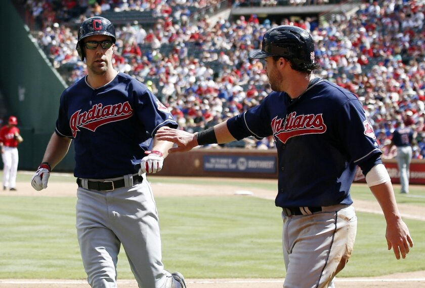 Cleveland Indians' Jason Kipnis (22) is congratulated by David Murphy after scoring on Murphy's sacrifice-fly against the Texas Rangers during the fourth inning of a baseball game, Saturday, June 7, 2014, in Arlington, Texas. (AP Photo/Jim Cowsert)