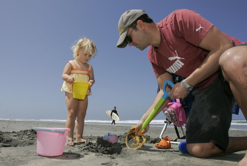 Jon Kochik and daughter Ruby, 2, of Cardiff play at Fletcher Cove in Solana Beach on Thursday, taking advantage of the May sunshine.