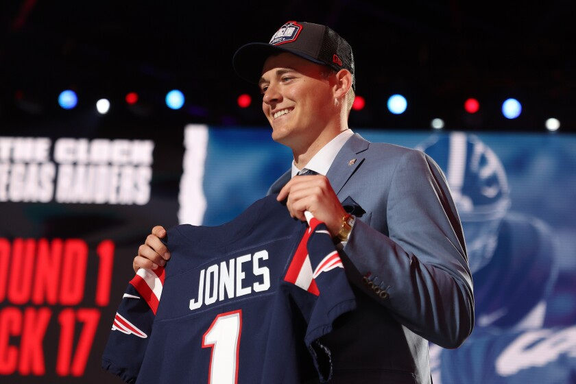 Mac Jones poses onstage after being selected 15th by the New England Patriots