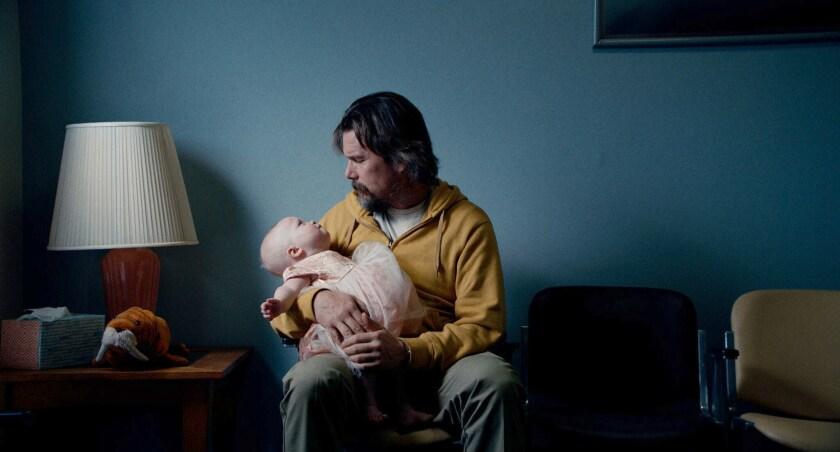 Ethan Hawke holds a baby in the movie 'Adopt a Highway'