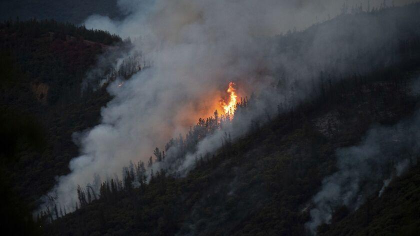 Flames from the Ferguson Fire burn down a hillside in unincorporated Mariposa County Calif., near Yo