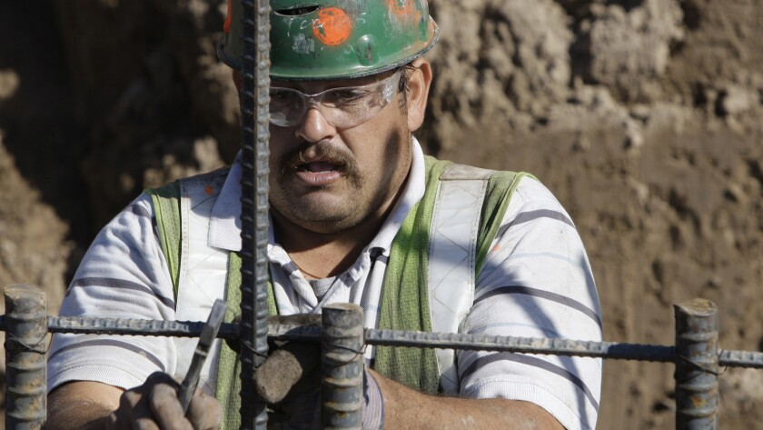 An unidentified worker connects rebar for the concrete foundation of the border wall in Granjeno, T