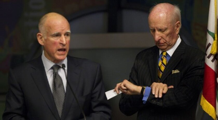 George Mitrovich, right, checks his watch while then-Gov. Jerry Brown speaks in Balboa Park. Founder and president of the City Club of San Diego, Mitrovich organized many forums featuring political and literary figures.