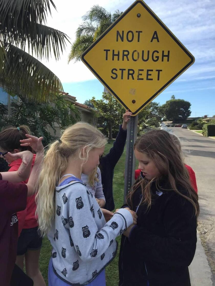 Girl Scouts Zoe Storm and Ella Seidel from Dana Middle School examine a geocache they found attached to a street sign.