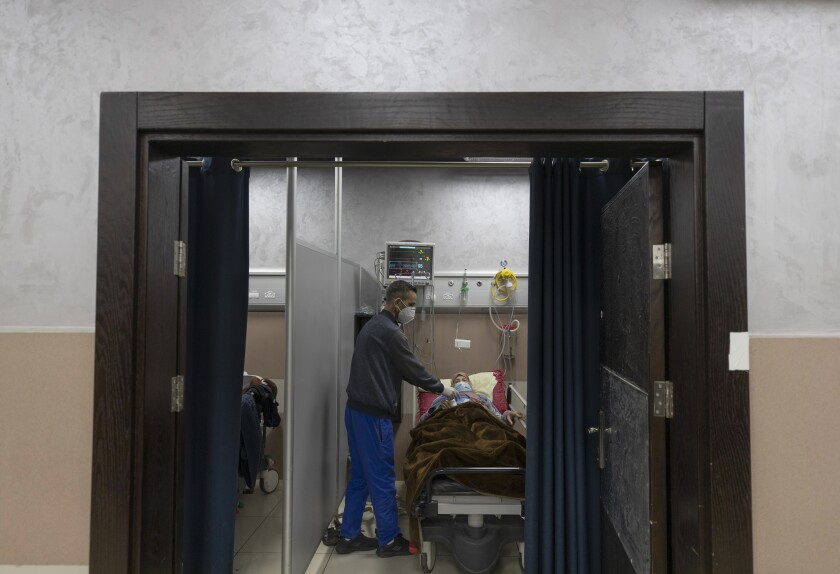 A medical staffer attends a Palestinian patient infected with COVID-19 at the emergency unit, of the Palestine Medical Complex, in the West Bank city of Ramallah, Tuesday, March 2, 2021. (AP Photo/Nasser Nasser)
