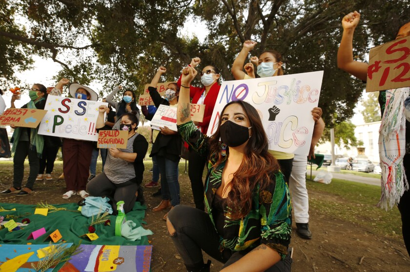 Women wearing masks raise their fists in a protest at a park