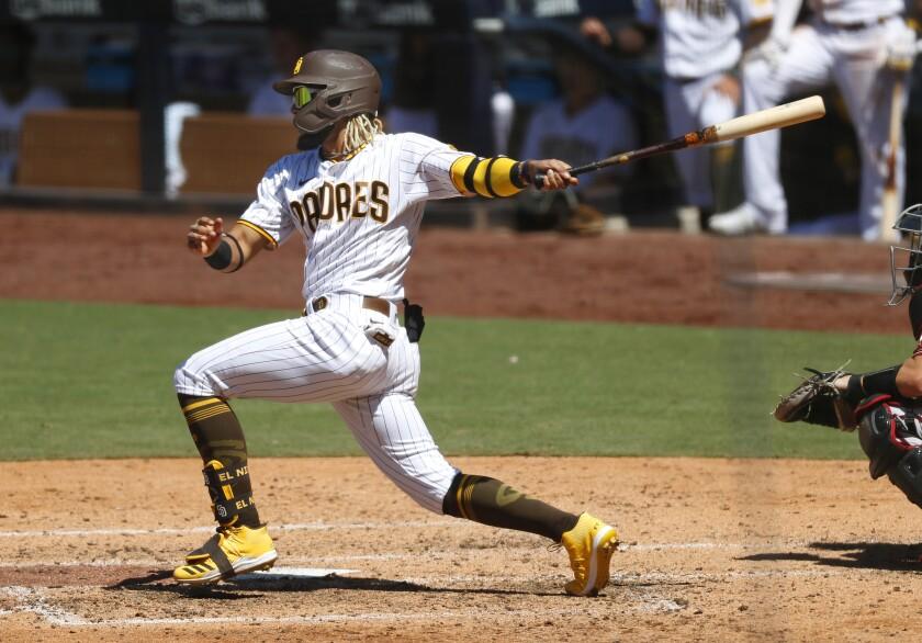 Fernando Tatis Jr. hits a three-run triple during the fourth inning of Monday's game.