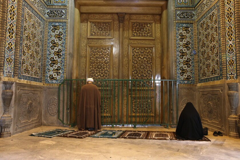 Two people pray March 16 behind a closed door at Masumeh shrine in Qom, 80 miles south of Tehran. Authorities closed the site, prompting angry demonstrations.