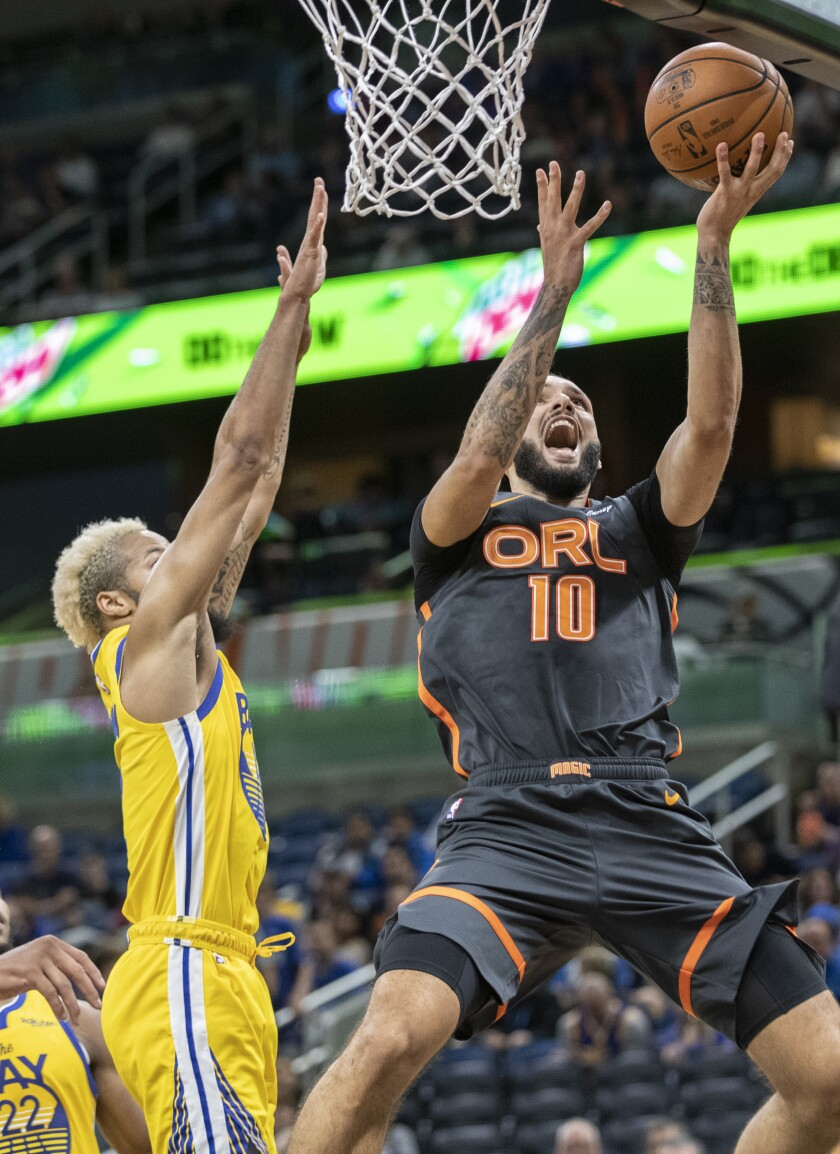 Orlando Magic guard Evan Fournier (10) takes the ball to the hoop on Golden State Warriors guard Ky Bowman (12) during the first half of an NBA basketball game, Sunday, Dec. 1, 2019, in Orlando, Fla. (AP Photo/Willie J. Allen Jr.)