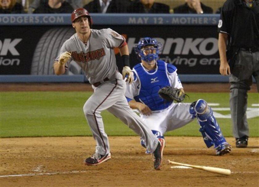 Arizona Diamondbacks' Paul Goldschmidt, left, hits a two-run home run as Los Angeles Dodgers catcher Ramon Hernandez looks on during the ninth inning of their baseball game, Tuesday, May 7, 2013, in Los Angeles. (AP Photo/Mark J. Terrill)