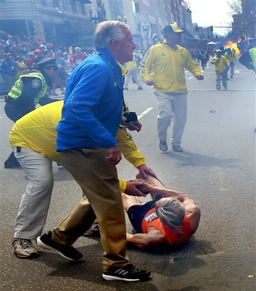 ADDS IDENTIFICATION OF RUNNER- BILL IFFRIG- Bill Iffrig, 78, lies on the ground as police officers react to a second explosion at the finish line of the Boston Marathon in Boston, Monday, April 15, 2013. Iffrig, of Lake Stevens, Wash., was running his third Boston Marathon and near the finish line