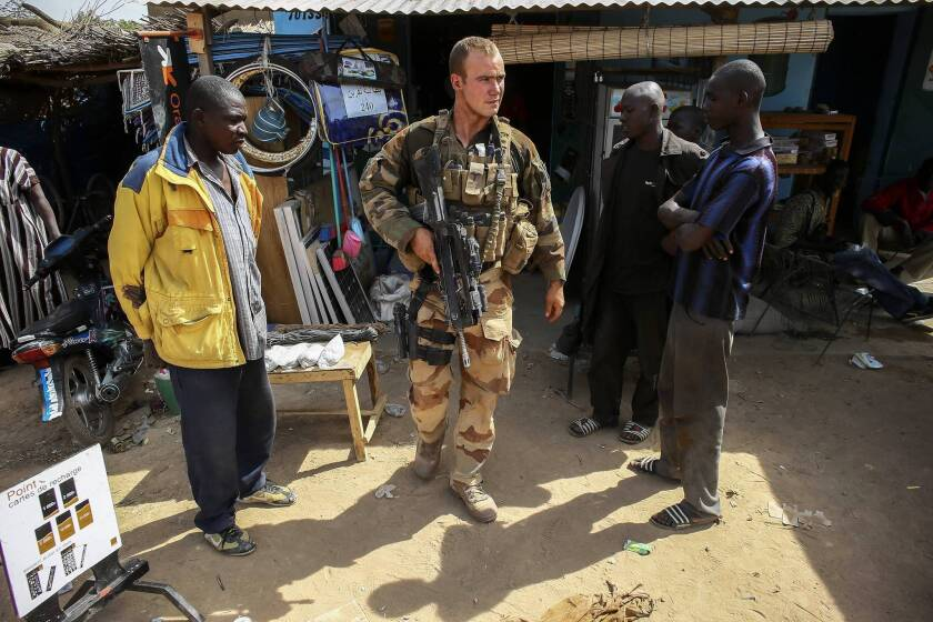 Malians watch a French soldier as he leaves a shop in the recently liberated town of Diabaly.