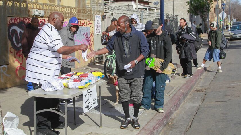 Hal Sadler, the San Diego Sock Man, hands out socks and message of love to people near 17th Street and Imperial Avenue on Tuesday morning in San Diego. A thankful Sadler, who was formerly homeless, wants to give back to the community.