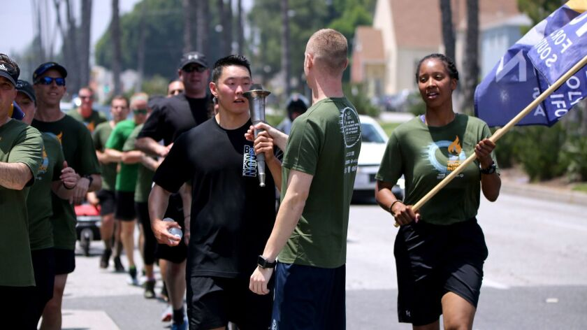 Burbank Police officer Scott Choe, left, passes the torch to Glendale Police officer Dacota Cummings