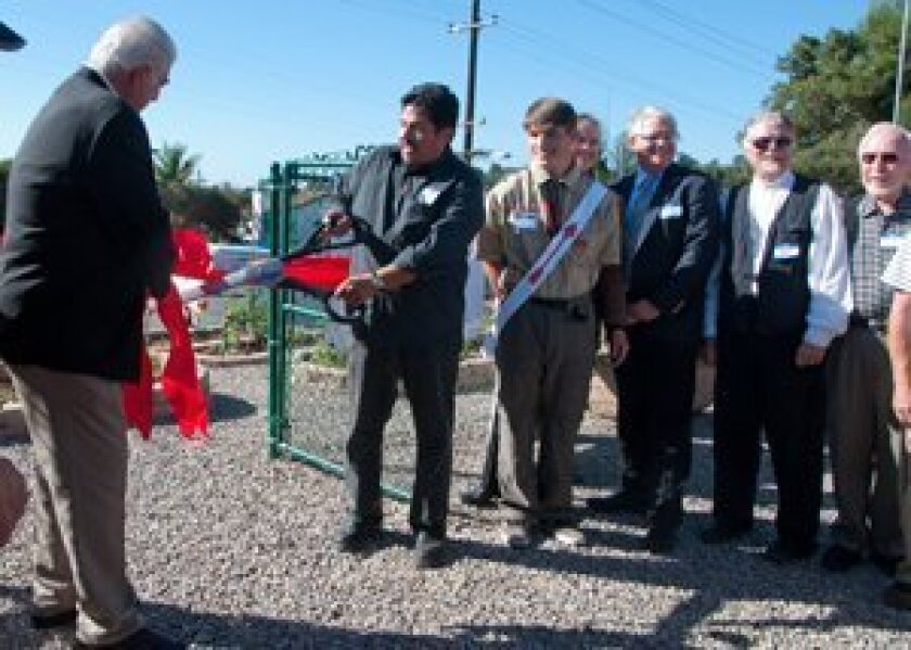 Manny Aguilar of the La Colonia de Eden Gardens foundation cuts the ribbon at the launch of the community garden at St. Leo Mission Catholic Church