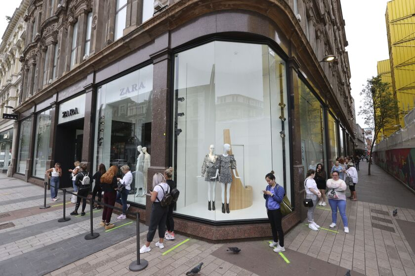 Shoppers queue outside Zara in Belfast, northern Ireland, Monday, June 15, 2020. After three months of being closed under coronavirus restrictions, shops selling fashion, toys and other non-essential goods are being allowed to reopen across England for the first time since the country went into lockdown in March. (Liam McBurney/PA via AP)