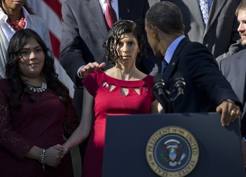 President Barack Obama offers a steadying hand to Karmel Allison of San Diego after she nearly fainted on stage during his Monday morning press conference on health reform in the Rose Garden at the White House.