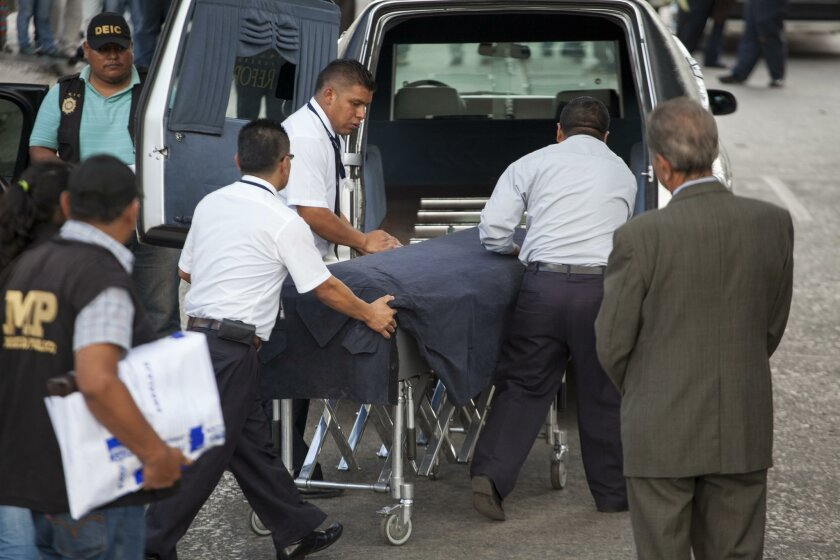Funeral home workers load the body of Francisco Palomo, lawyer of former dictator Efrain Rios Montt into a funeral car, in Guatemala City, Wednesday, June 3, 2015. Palomo was shot at least 12 times in the chest and thorax while driving around midday, firefighters' spokesman Raul Hernandez said. Pal