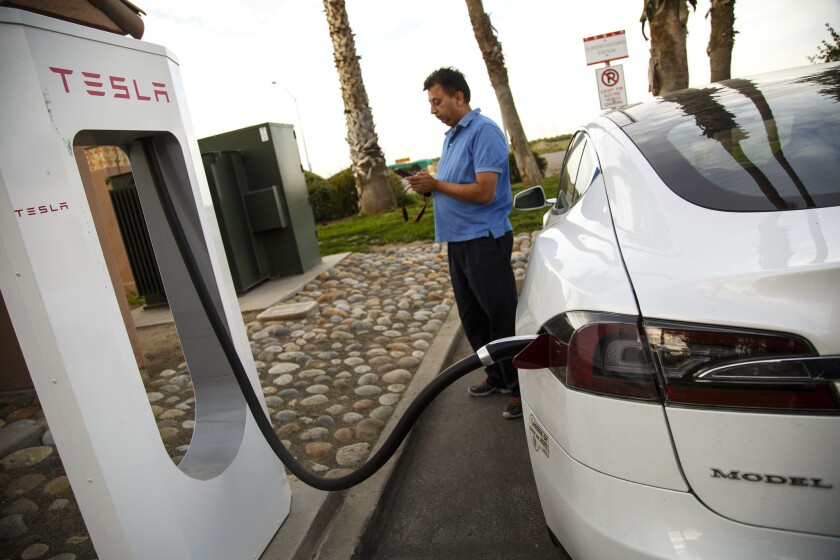 A man stands next to a Tesla charging station, his car plugged in.