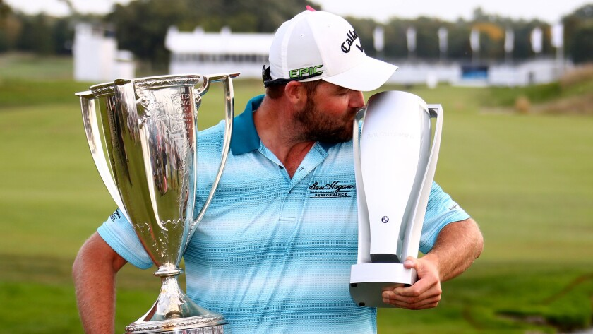 Marc Leishman celebrates with his trophies after winning the BMW Championship at Conway Farms Golf C