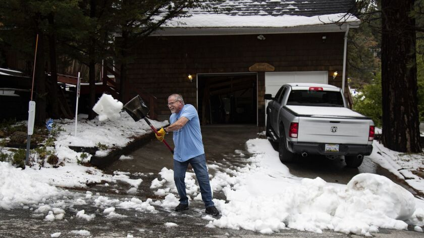 RUNNING SPRINGS, CA - MAY 20, 2019: Paul Gill of Running Springs shovels snow at the end of his driv