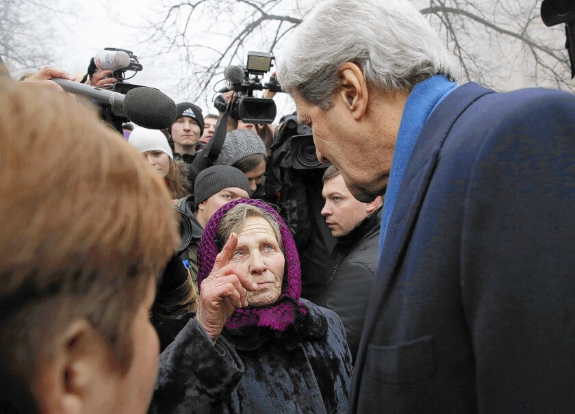 A Ukrainian woman speaks with U.S. Secretary of State John F. Kerry in Kiev as he visits a shrine to people killed during the recent political uprising.