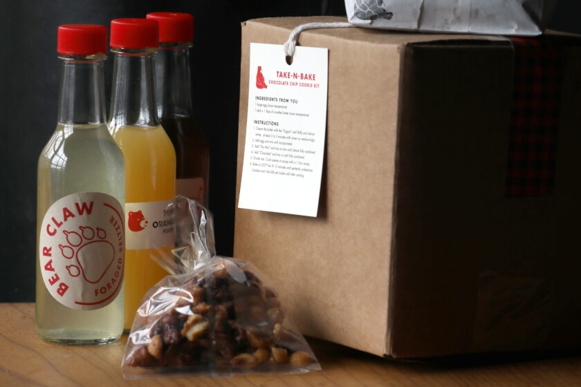 Small bottles of cocktail ingredients, with a bag and box of to-go food