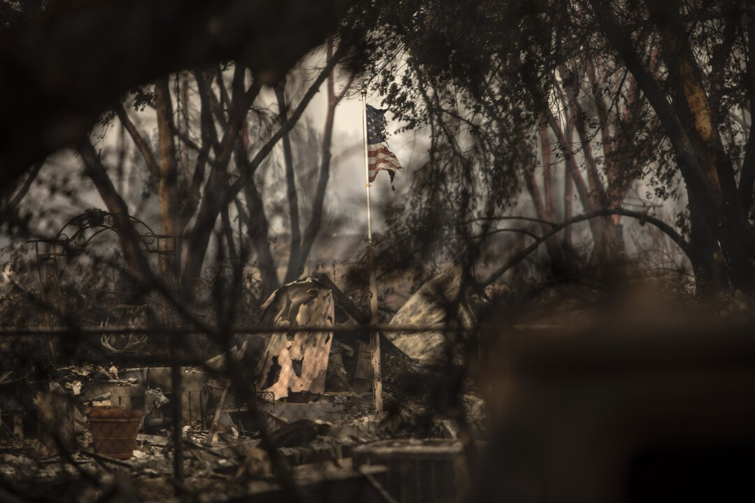 A burned flag flies in what is left of Talent Mobile Estates, following the Almeda fire in southern Oregon.