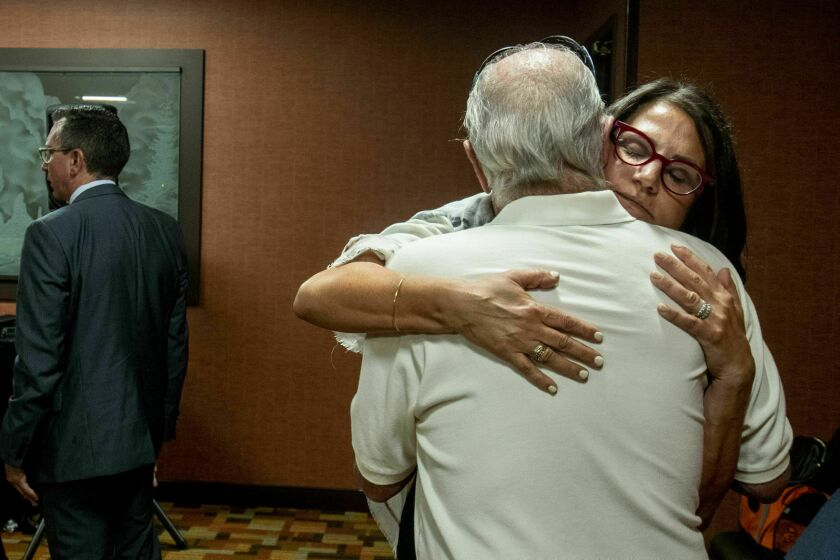 FILE - In this July 11, 2019 file photo, Tanya Gersh, a Montana real estate agent, embraces her father Lloyd Rosenstein following a hearing at the Russell Smith Federal Courthouse in Missoula. The real estate agent's attorneys are eyeing the assets of a neo-Nazi website operator to collect on a $14 million court judgment against the man for an anti-Semitic harassment campaign that he orchestrated online against the Jewish woman and her family. (Ben Allen/The Missoulian via AP)