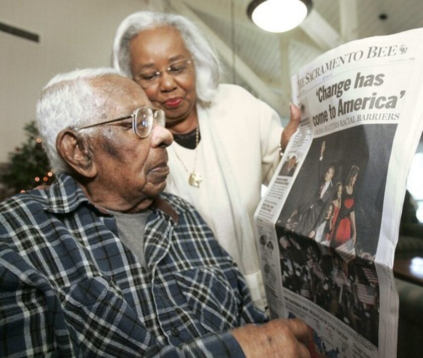 The politically-minded George Francis, who voted for Barack Obama, looks at a newspaper of his victory with daughter Lelia LaRue. Francis was born in 1896 and grew up in the South, affected by the nation's racially oppressive Jim Crow laws.