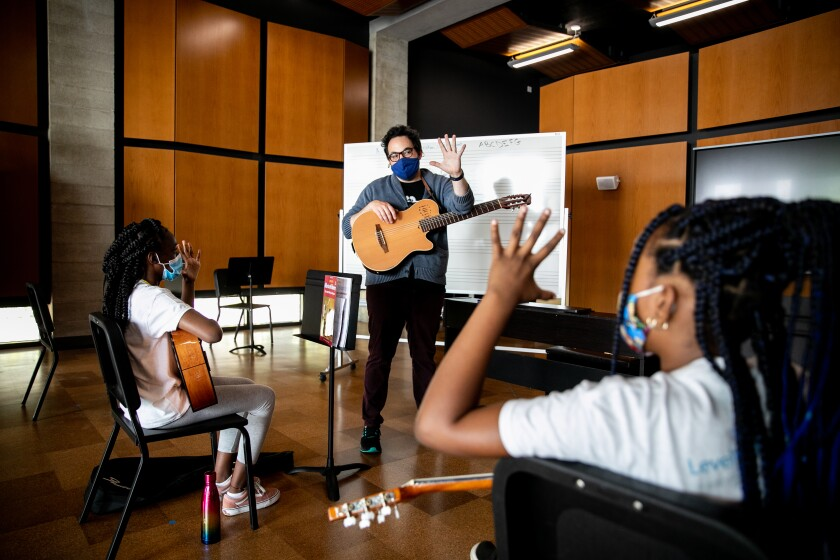 Nico Hueso, a teacher with the San Diego Youth Symphony, teaches students mariachi Monday