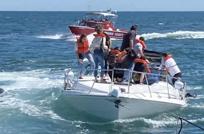 More than a dozen people await rescue on a sinking boat, a 41-foot Carver vessel.