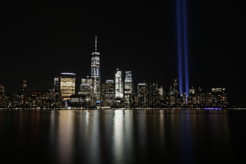 FILE - In this Sept. 11, 2017, file photo, the Tribute in Light illuminates in the sky above the Lower Manhattan area of New York, as seen from across the Hudson River in Jersey City, N.J. The coronavirus pandemic has reshaped how the U.S. is observing the anniversary of 9/11. The terror attacks' 19th anniversary will be marked Friday, Sept. 11, 2020, by dueling ceremonies at the Sept. 11 memorial plaza and a corner nearby in New York. (AP Photo/Jason DeCrow, File)