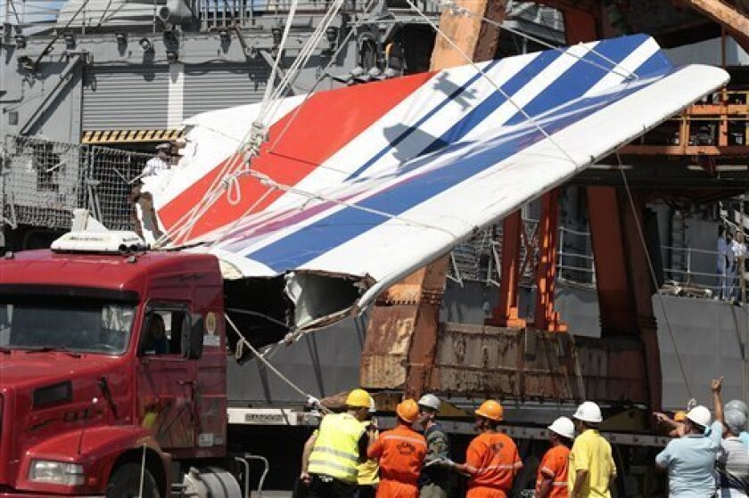 FILE -- In this Sunday, June 14, 2009 file photo workers unload debris belonging to crashed Air France flight AF447 from the Brazilian Navy's Constitution Frigate in the port of Recife, northeast of Brazi. More than 600 pieces of Air France Flight 447 are being sent from Brazil to France by ship to be studied further for clues to the June 1 crash, Airbus said Thursday July 9, 2009. The disaster overshadowed a meeting of Air France-KLM shareholders on Thursday, with pilots saying the company didn't do enough to prevent the plane from crashing into the Atlantic Ocean. All 228 people aboard were killed and the reason for the accident remains unclear. (AP Photo/Eraldo Peres, File)