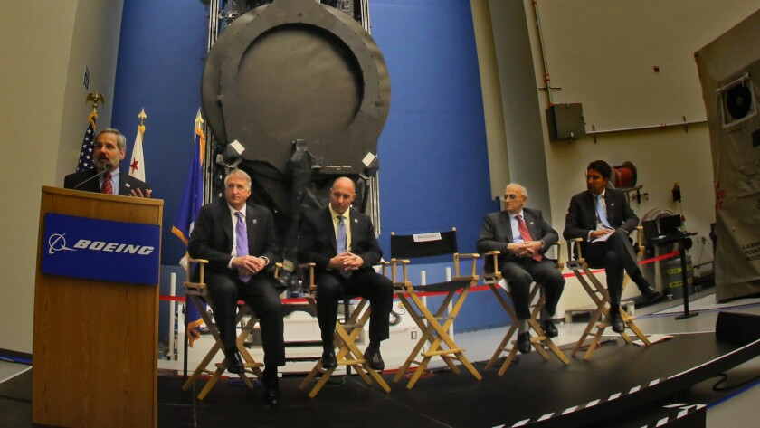 Boeing executive Mike Connelly, left, unveils the world's first all-electric-propulsion satellites at Boeing's El Segundo satellite division in January.
