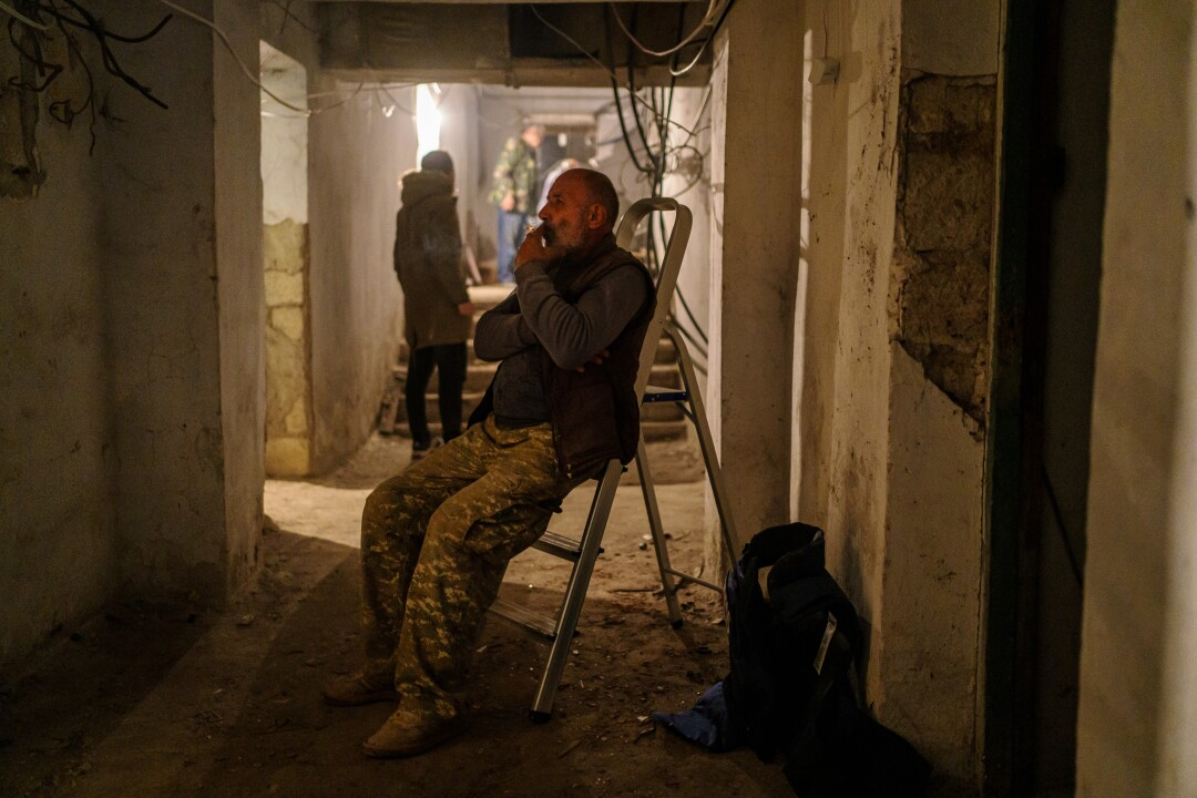 A man takes a cigarette break in an underground bunker as bombing sirens are wailing.