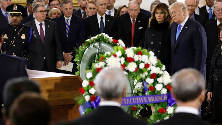 President Donald Trump and First Lady Melania Trump pay their respects at the casket together as the