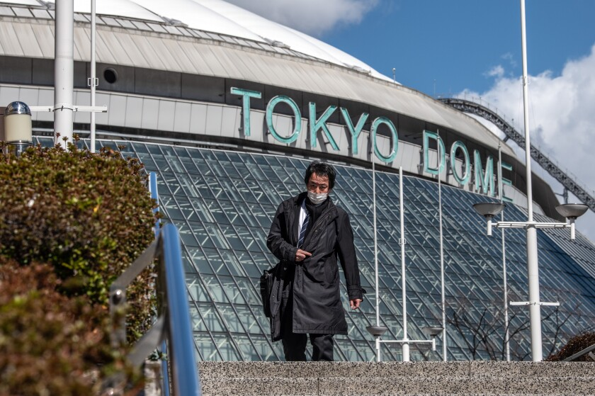 A man wearing a face mask walks past the Tokyo Dome, where baseball games will no longer be played in front of crowds because of coronavirus fears.