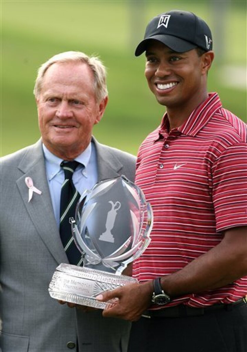FILE - In this June 7, 2009 file photo, Tiger Woods, right, holds the trophy next to Jack Nicklaus after winning the Memorial golf tournament in Dublin, Ohio. After winning his 17th major, a 40-year-old Nicklaus withdrew from the final round of the World Series of Golf because of a bad back _ the first injury of his career. Woods had his fourth knee surgery a week after winning his 14th major, his pursuit of Nicklaus' record now looking even longer.(AP Photo/Mike Munden, File)