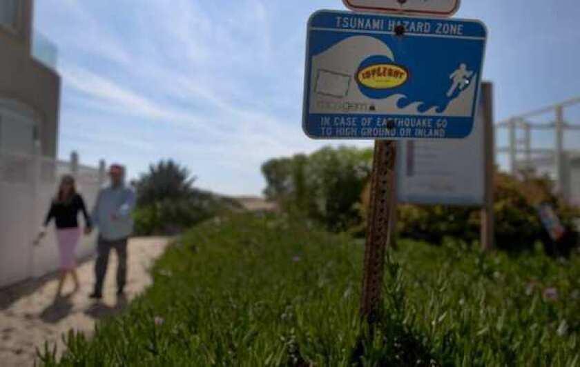 A couple walks past a tsunami warning sign at Sunset Beach.