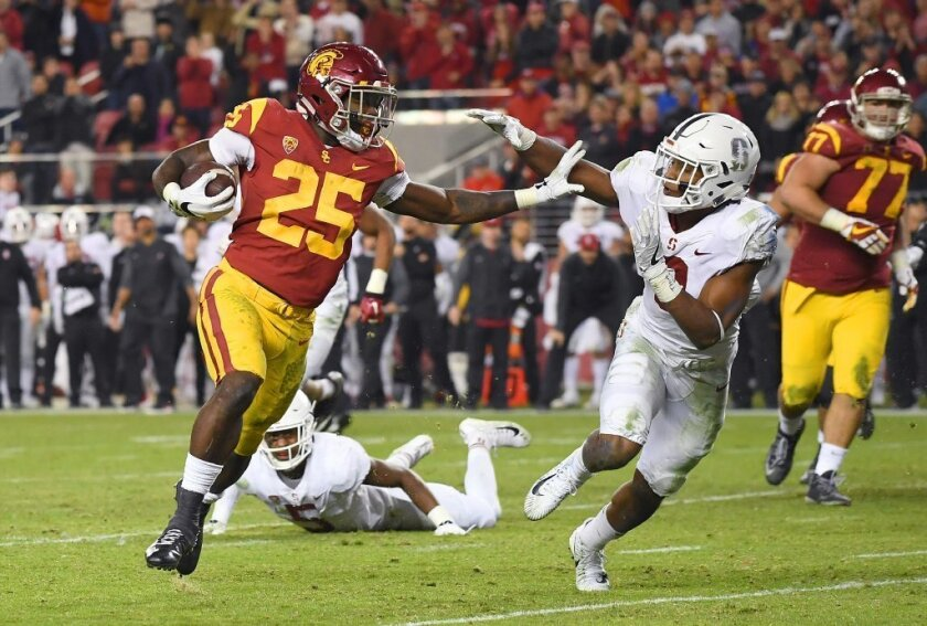 USC running back Ronald Jones II fights off a tackle attempt by Stanford's Justin Reid as he runs for an eight-yard touchdown during the Pac-12 championship game at Levi's Stadium on Dec. 1.
