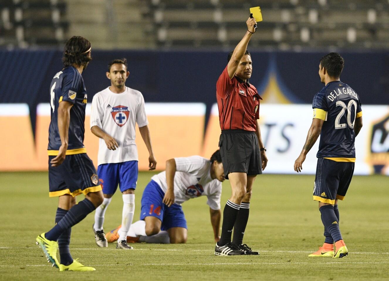 Jun 14, 2016; Los Angeles, CA, USA; Referee Ramon Hernandez gives LA Galaxy defender A.J. DeLaGarza (20) a yellow card during the second half against La Maquina at StubHub Center. The LA Galaxy won 4-1. Mandatory Credit: Kelvin Kuo-USA TODAY Sports ** Usable by SD ONLY **