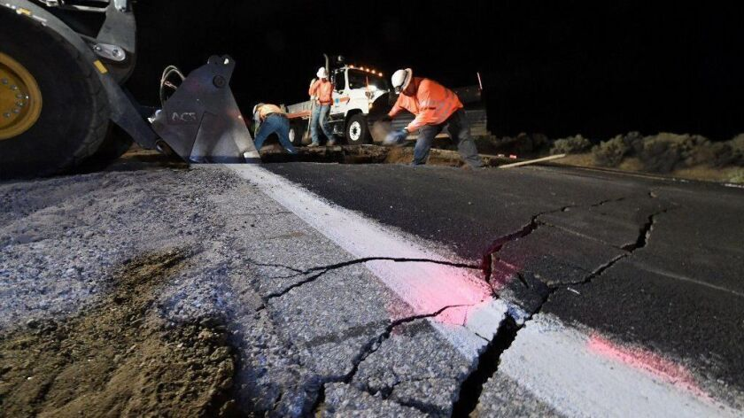 Highway workers repair part of a road damaged by the magnitude 7.1 earthquake on July 5 near Ridgecrest, Calif.