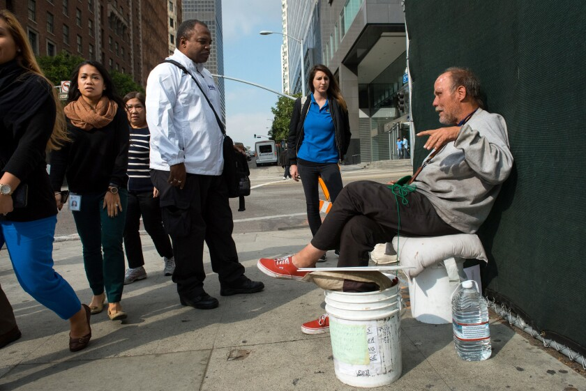 Outreach workers John Johnson from Chrysalis and Sydney Sheiner from PATH talk with Richard Bailey, who used to be homeless but now has housing in Van Nuys. Bailey returns to Pershing Square to crochet.