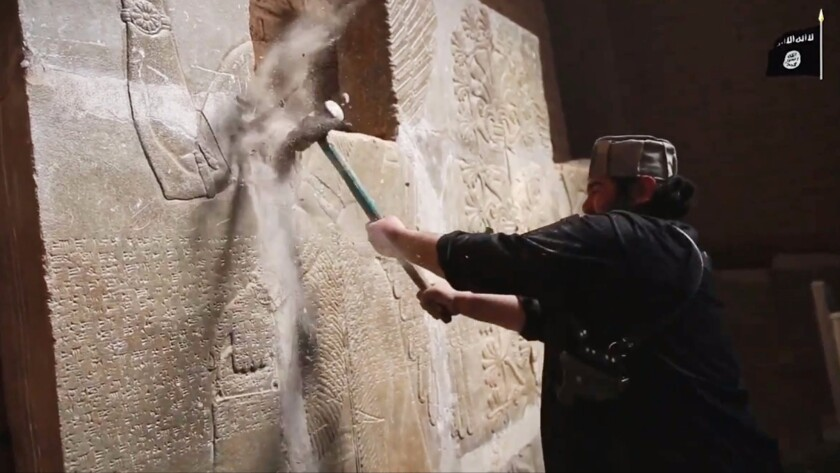 An undated screen grab from video released by Islamic State reportedly shows a member destroying parts of a frieze at the ancient Iraqi town of Nimrud, southeast of Mosul.