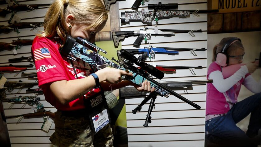 "Addyson ""Alpha Addy"" Soltau, 9, tries out rifles in the Keystone Sporting Arms booth at the National Rifle Assn. convention in Dallas on May 6."