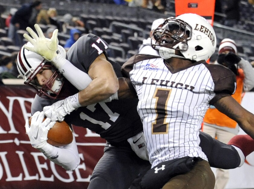 FILE - In this Nov. 22, 2014, file photo, Lafayette wide receiver Matt Mrazek, left, catches a touchdown pass as Lehigh cornerback Oliver Riguad defends during the second half of an NCAA college football Patriot League game at Yankee Stadium in New York. The Patriot League joined the Ivy League on Monday, July 13, 2020, punting on a fall football season because of the coronavirus pandemic while holding out hope that it could be made up in the second academic semester. (AP Photo/Bill Kostroun, File)